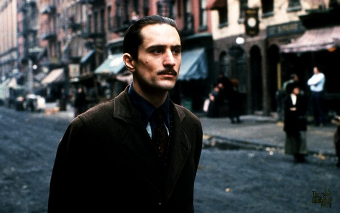 Photographie de Robert De Niro dans Le Parrain, Deuxième partie. L'acteur est pris dans une rue du New York du début du siècle et marche avec un air calme et observateur.
