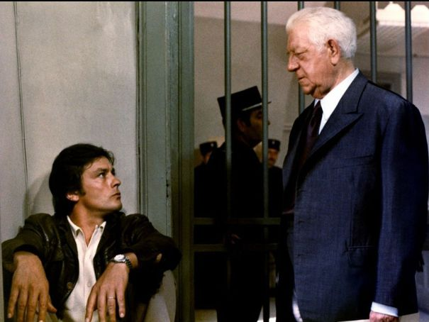 Photo d'Alain Delon et Jean Gabin dans le film Deux hommes dans la ville. Le premier est assis dans une cellule de prison alors que le second vient lui rendre visite.