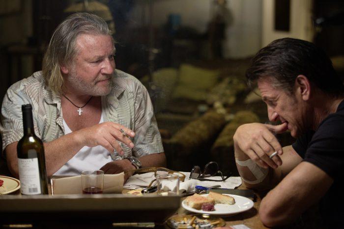 Photo de Ray Winstone et Sean Penn dans le film Gunman. Les deux acteurs sont assis autour d'une table et semblent discuter sérieusement en fumant une cigarette.