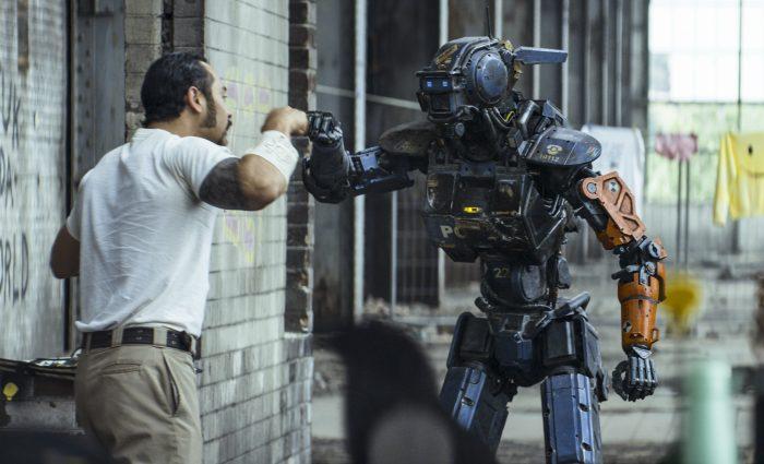 Photo de Jose Pablo Cantillo et Sharlto Copley dans le film Chappie de Neil Blomkamp. Le gangster et le robot sont en train de faire un check amical.