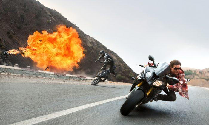 Photo de Tom Cruise dans le film Mission: Impossible - Rogue Nation de Christopher McQuarrie. L'acteur effecture un virage serré lors d'une course poursuite en moto. Au second plan, nous pouvons voir une explosion ainsi qu'un second motard expulsé de son engin.