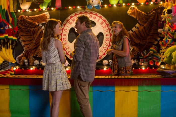 Photographie du film L'homme irrationnel de Woody Allen. Emma Stone et Joaquin Phoenix rient ensemble et s'apprêtent à participer à un stand de fête foraine. La photo est très colorée.