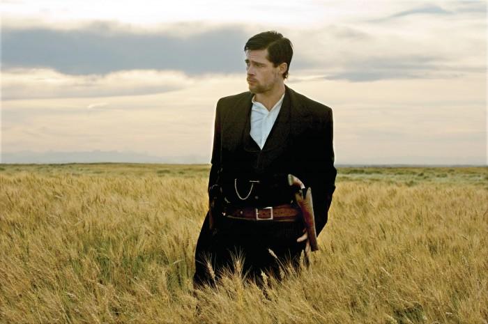 Photographie de Brad Pitt dans le film L'assassinat de Jesse James par le lâche Robert Ford d'Andrew Dominik. Jesse James se tient debout dans un champs et scrute l'horizon.