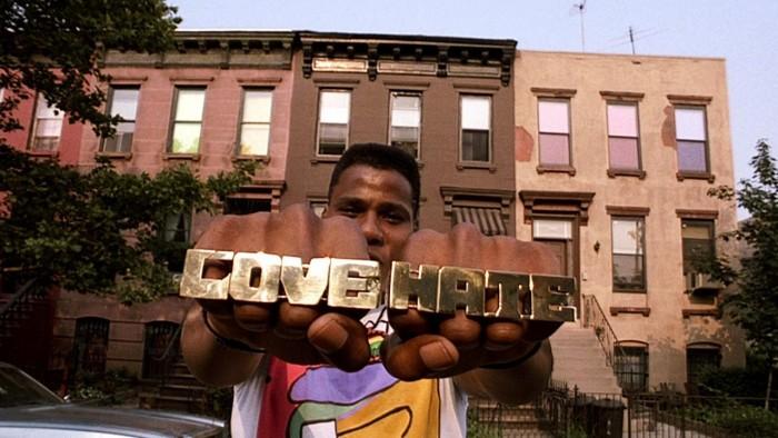 Photographie de Radio Raheem dans le film Do The Right Thing de Spike Lee. Face à l'objectif, le personnage montre ses poings sur lesquels figurent ses bagues Love/Hate. Hommage à La nuit du chasseur.