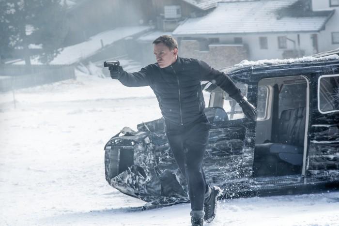 Photographie du film Spectre de Sam Mendes. Nous y voyons James Bond, incarné par Daniel Craig, courir en visant avec son arme dans la neige. Un hélicoptère est crashé derrière lui.