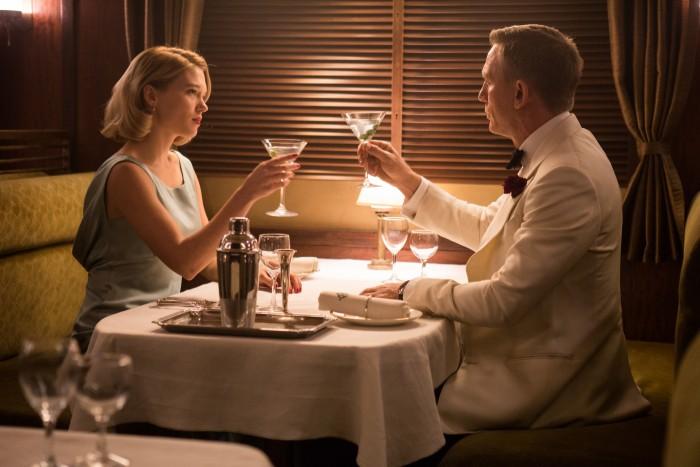 Photographie de Léa Seydoux et Daniel Craig dans le fillm 007 Spectre de Sam Mendes. Ils trinquent à la table d'un restaurant dans un train.
