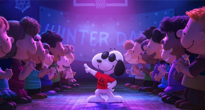 Photographie du fim Snoopy et les Peanuts. Snoopy porte des lunettes de soleil et dans lors d'une fête. Ses amis sont autour de lui et l'encouragent.