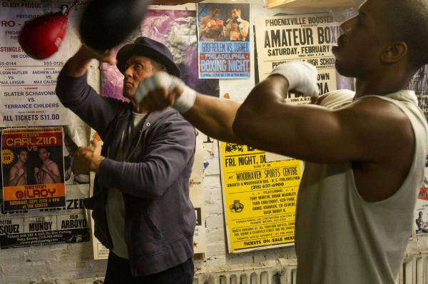 Photo du film Creed, réalisé par Ryan Coogler. Nous pouvons voir Sylvester Stallone et Michael B. Jordan s'entraîner à la boxe dans un gymnase.