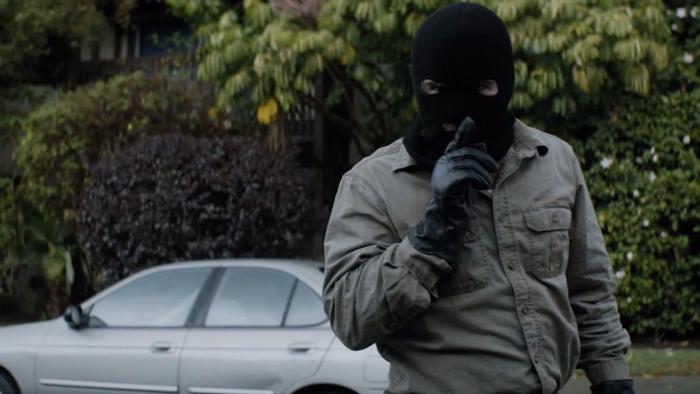 Photographie de la saison 2 de True Detective. Nous y voyons le personnage interprété par Colin Farrell, masqué par une cagoule et faisant signe de se taire avec un air menaçant.