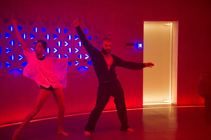 Photo de Sonoya Mizuno et Oscar Isaac dans le film Ex Machina d'Alex Garland. Nous voyons les personnages en train de danser dans une pièce fermée avec des lumières rouges et bleues.