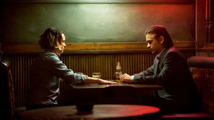 Photographie de la saison 2 de True Detective. Nous y voyons les personnages interprétés par Rachel McAdams et Colin Farrell, assis dans un bar en train de discuter face-à-face.