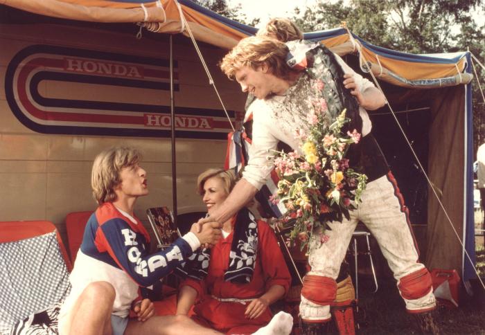 Photographie du film Spetters réalisé par Paul Verhoeven. Nous y voyons Rutger Hauer qui interprète un champion de moto dans le film et qui salue ici l'un de ses admirateurs.