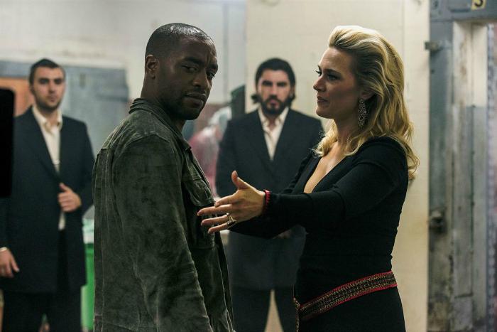 Photo de Chiwetel Ejiofor et Kate Winslet dans le film Triple 9 de John Hillcoat. Ils discutent. Ejiofor semble surpris et choqué alors que Winslet est paraît sereine.