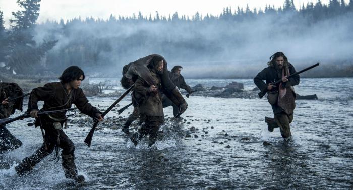 Photographie du film The Revenant. Nous y voyons le personnage incarné par Leonardo DiCaprio ainsi que d'autres protagonistes courir dans l'eau armés de fusils. DiCaprio porte un homme blessé sur son dos.