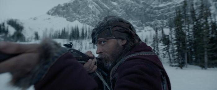 Photographie de Tom Hardy dans le film The Revenant. Armé d'un fusil, nous pouvons voir le comédien en train de viser.