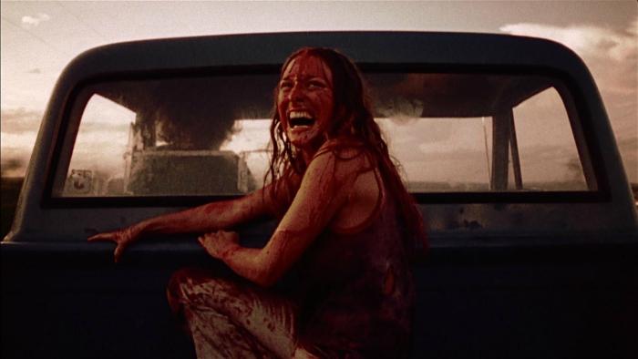 Photographie de Marilyn Burns dans Massacre à la tronçonneuse de Tobe Hooper. Sur la photo, l'actrice est à bord d'un équipe et regard à l'arrière de la route avec un air terrifié. Son corps et son visage sont recouverts de sang.