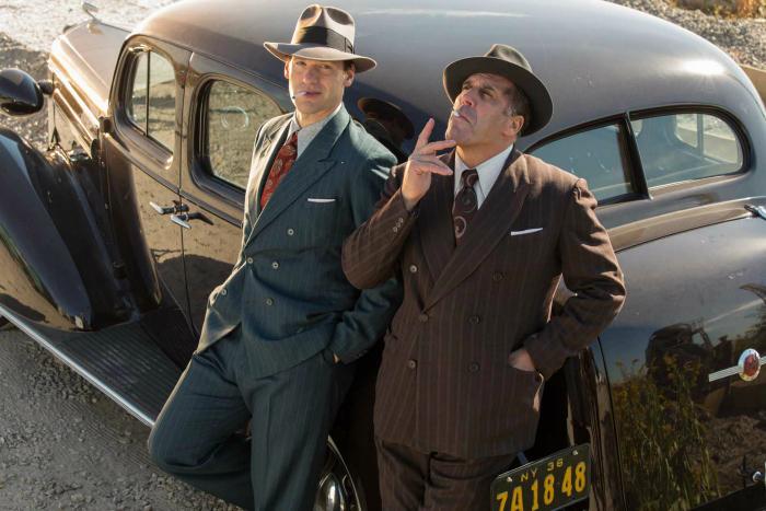 Photo de Corey Stoll dans Café Society de Woody Allen. Le comédien est adossé à une voiture et discute avec l'un de ses amis gangsters.