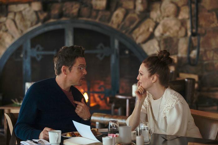 Photo d'Ethan Hawke et Julianne Moore dans le film Maggie a un plan de Rebecca Miller. Les deux acteurs discutent à la table d'un restaurant.