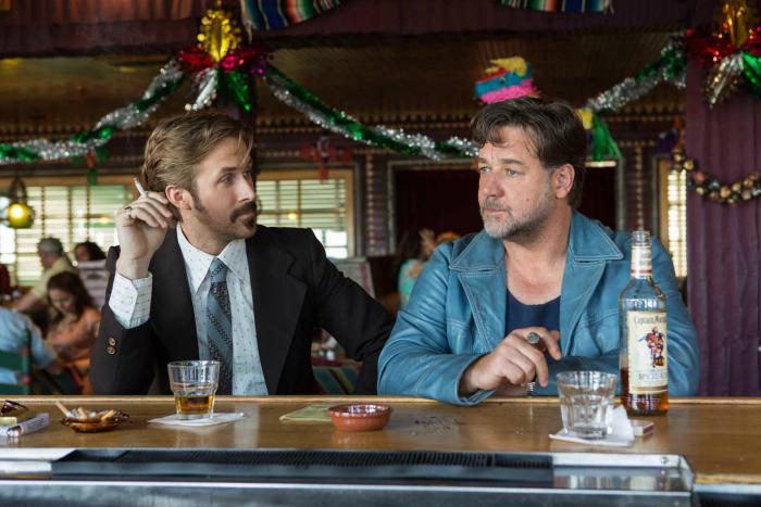Photo de Ryan Gosling et Russell Crowe dans The Nice Guys de Shane Black. Les deux détectives boivent un verre au comptoir d'un bar.