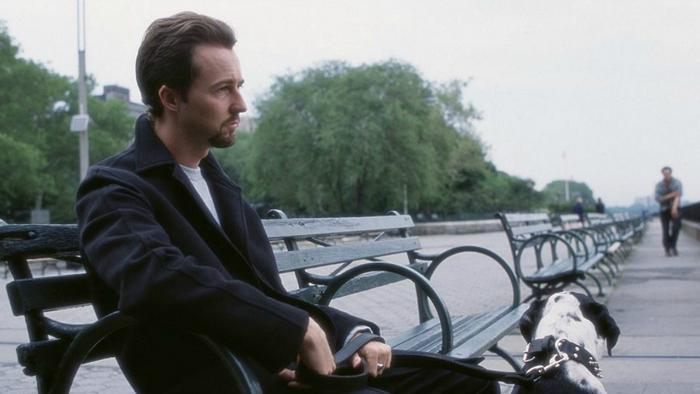 Photo d'Edward Norton dans le film La 25ème heure de Spike Lee. L'acteur promène son chien sur les rives de Manhattan et est assis sur un banc.