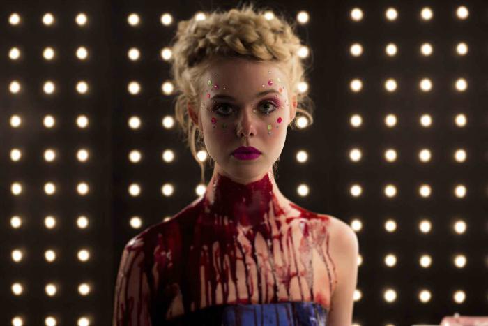 Photo d'Elle Fanning dans le film The Neon Demon de Nicolas Winding Refn. L'actrice est face à l'objectif pour un photoshoot, maquillée avec pleine de sang, comme si elle avait la gorge tranchée.