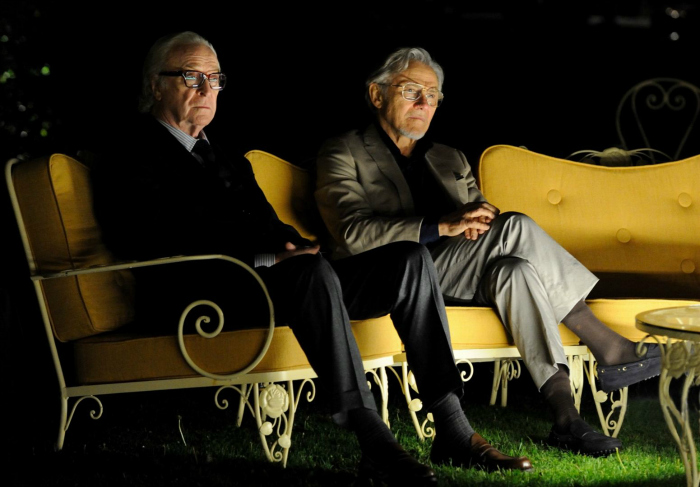 Photo de Michael Caine et Harvey Keitel dans le film Youth de Paolo Sorrentino. les deux comédiens sont face à l'objectif, assis dans un somptueux canapé installé dans un jardin et semblent regarder un spectacle de nuit.