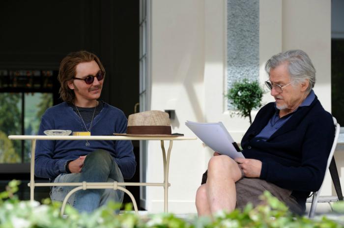 Photo de Paul Dano et Harvey Keitel dans le film Youth de Paolo Sorrentino. Sur un balcon, Keitel fait la lecture d'un scénario à Dano qui semble apprécier le texte.