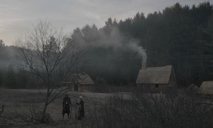 Photo de The Witch sur laquelle nous voyons les deux parents travailler la terre près de leur maison.