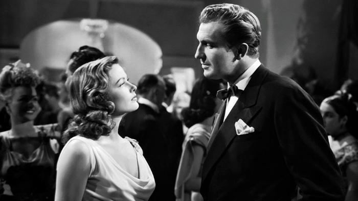 Photo de Gene Tierney et Vincent Price dans le film Laura d'Otto Preminger. Les deux acteurs sont face à face lors d'une soirée dans un appartement.