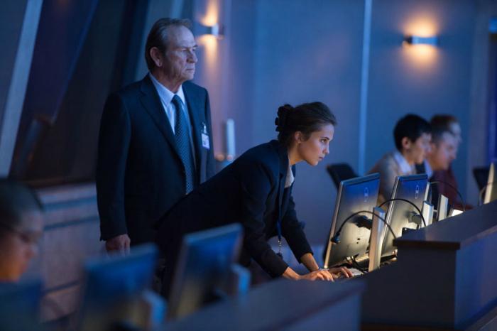 Photo de Tommy Lee Jones et Alicia Vikander dans le film Jason Bourne de Paul Greengrass. Alors qu'il dirige une mission dans les locaux de la CIA, Vikander donne un ordre en parlant dans un micro.