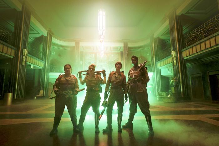Photo du film S.O.S Fantômes réalisé par Paul Feig. Les quatre actrices prennent la pose face à l'objectif devant un immense jet de lumière verte.