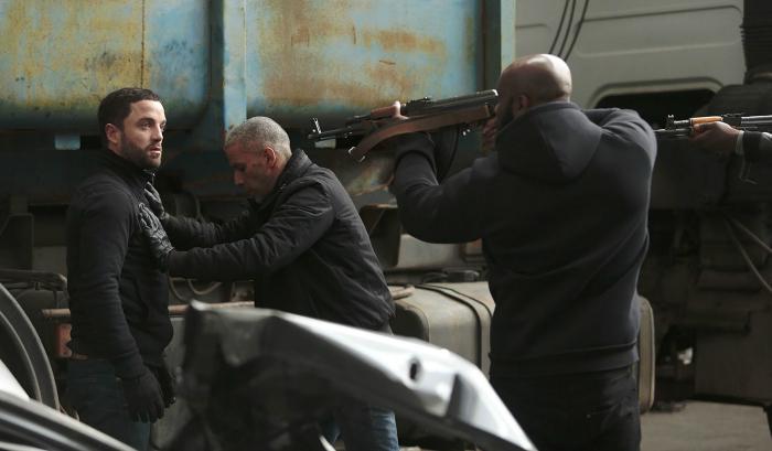 Photo de Guillaume Gouix, Sami Bouajila et Kaaris dans le film Braqueurs de Julien Leclercq. Kaaris braque avec une arme lourde les deux autres acteurs dans un hangar.