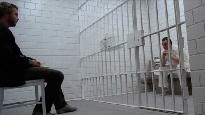 Photo de William Petersen et Brian Cox discutant dans la cellule protégée de Hannibal dans le film Manhunter de Michael Mann.