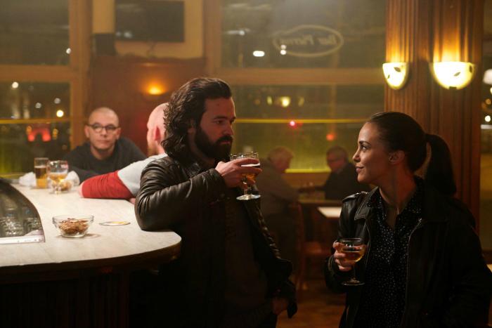 Photo de Romain Duris et Alice Belaïdi dans le film Un Petit Boulot de Pascal Chaumeil. Les deux acteurs discutent en buvant un bière au comptoir d'un bar.