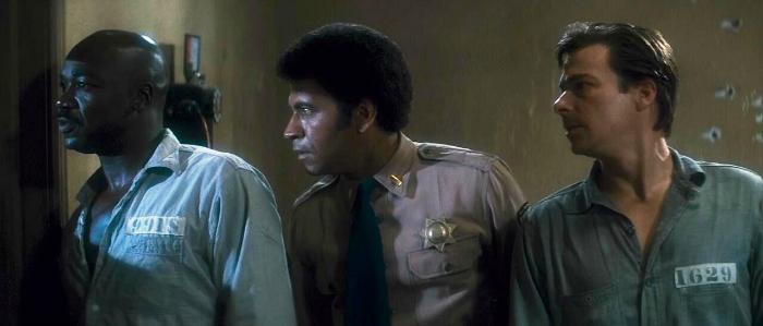 Photo d'Austin Stoker, Darwin Joston et Tony Burton observant côte à côte par la fenêtre dans le film Assaut de John Carpenter.