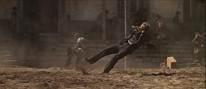 Photo d'un corps touché par balles qui tombe au ralenti dans le film La Horde Sauvage de Sam Peckinpah.