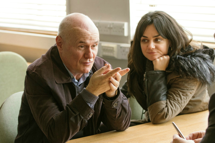 Photo de Dave Johns et Hayley Squires lors d'un entretien à l'agence d'emplois dans le film Moi, Daniel Blake de Ken Loach. Ils sont assis à une table côte à côte et Johns parle à un autre personnage.