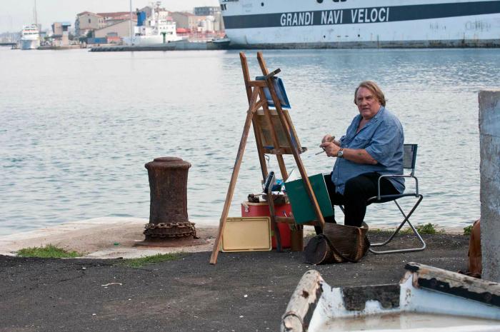 Photo de Gérard Depardieu en train de peindre sur un bord de mer.