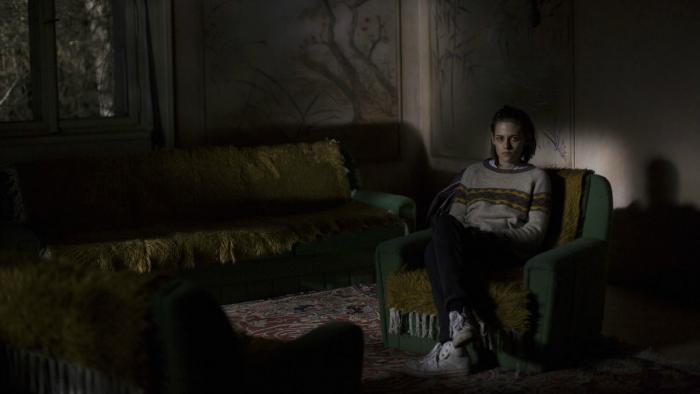 Photo de Kristen Stewart assise dans une pièce de manoir très sombre dans le film Personal Shopper d'Olivier Assayas.