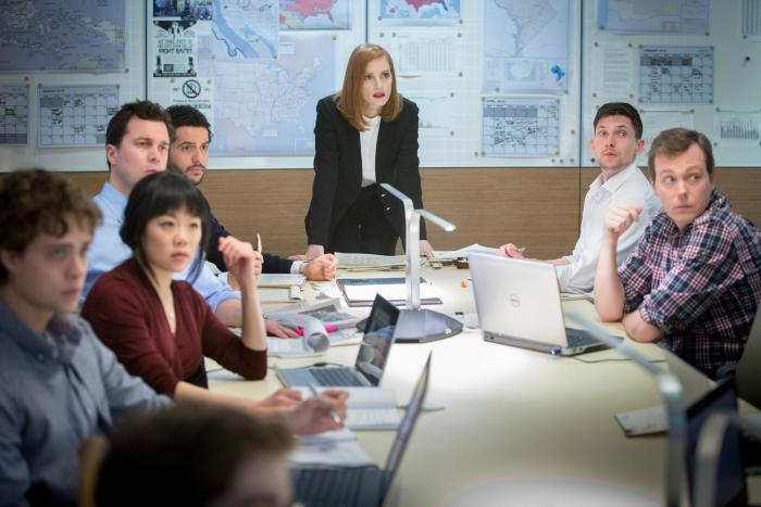Photo du film Miss Sloane sur laquelle Jessica Chastain s'adresse debout à ses collaborateurs qu'elle dirige et qui sont eux assis.