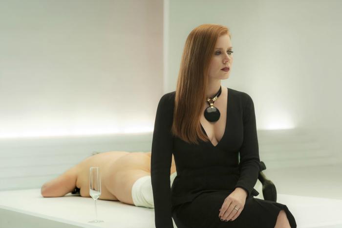 Photo d'Amy Adams dans le film Nocturnal Animals de Tom Ford. L'actrice est assise devant une femme nue, allongée et en pleine performance artistique. Elle semble perdue.