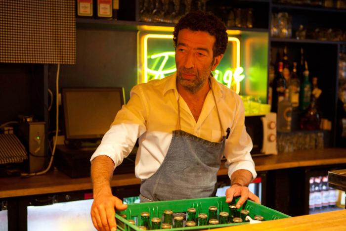 Photo de Slimane Dazi derrière son bar dans le film Les Derniers Parisiens d'Hamé et Ekoué.