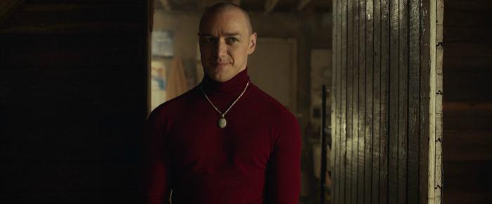 Photo de James McAvoy dans la peau de Patricia, l'une de ses 23 personnalités dans Split de M. Night Shyamalan. Patricia fait face à d'autres protagonistes dans des souterrains.