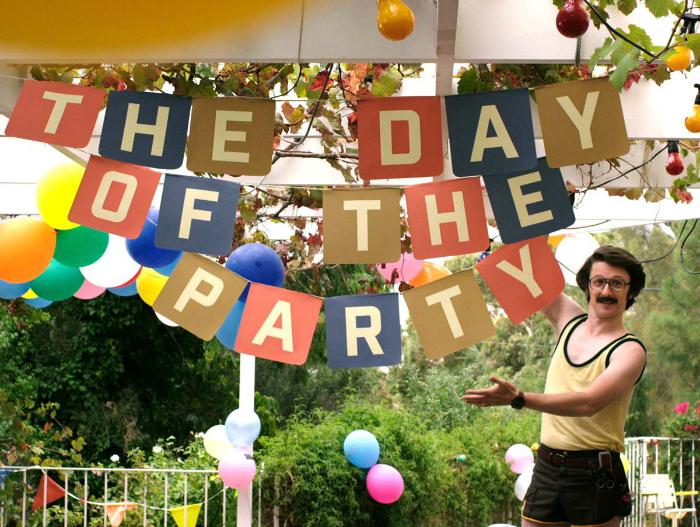 Photo de Matthew Whittet dans le film Fantastic Birthday de Rosemary Myers sur laquelle il montre fièrement une belle banderole d'anniversaire à sa fille.