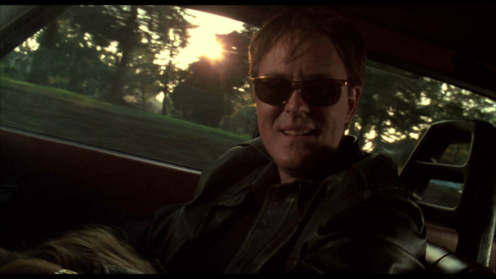 Photo de John Lithgow dans le rôle de Caïn dans L'esprit de Caïn de Brian De Palma. Le personnage est assis dans la voiture et discute avec Carter, son autre personnalité que l'on devine à la place du conducteur.
