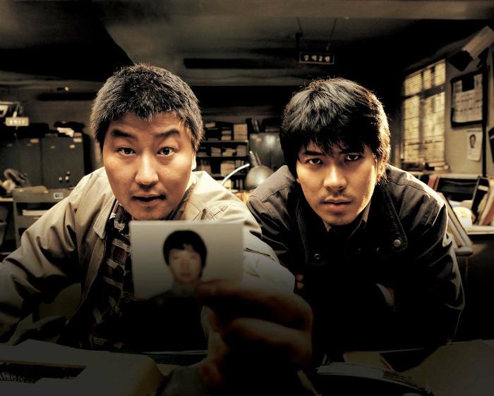 Photo des deux inspecteurs de Memories of Murder de Bong Joon-ho qui pointent la photo d'un suspect vers un témoin. Ils semblent extrêmement pressés d'entendre la réponse. La photo est prise du point de vue du témoin.
