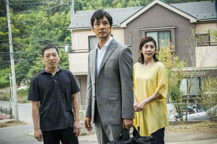 Photo de Hidetoshi Nishijima, Yuko Takeushi et Teruyuki Kagawa dans le film Creepy de Kiyoshi Kurosawa. Les trois personnages semblent en observer un quatrième dans leur quartier résidentiel.