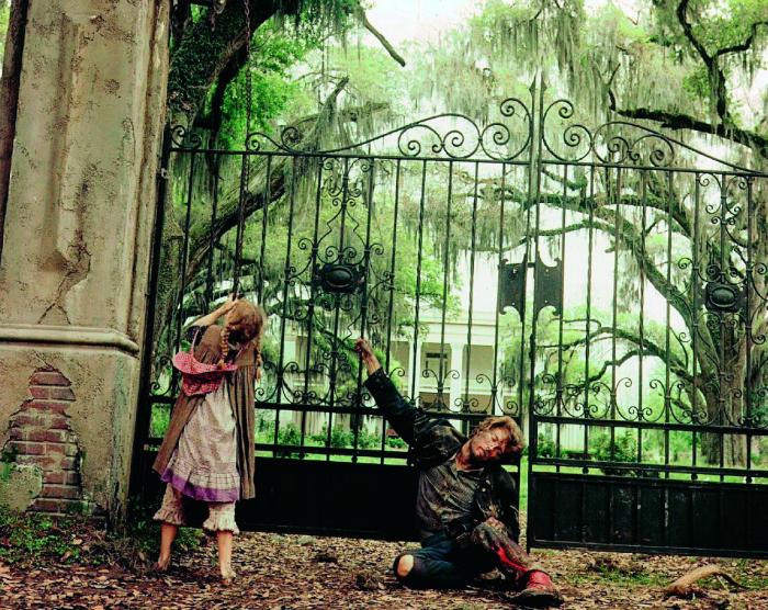 Photo tirée du film Les Proies de Don Siegel sur laquelle Clint Eastwood est blessé, assis devant le portail de la maison victorienne, accompagnée par Pamelyn Ferdin, l'interprète de la jeune Amy.