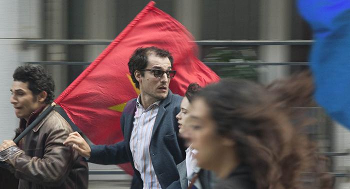 Photo de Louis Garrel en Jean-Luc Godard dans Le Redoutable où l'on voit le réalisateur courir lors d'une manifestation de mai 68.