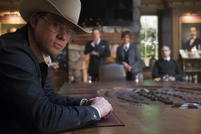 Photo de Channing Tatum dans Kingsman - Le cercle d'or sur laquelle Channing Tatum regarde l'objectif. Colin Firth, Halle Berry et Mark Strong sont floutés au second plan.